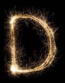 Fotografie English Letter D from sparklers alphabet on black background.