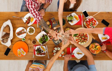 People say cheers clink glasses at festive table dinner party