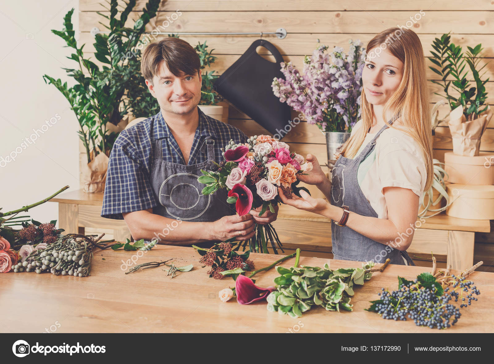 Florist and assistant in flower shop delivery make rose bouquet ...