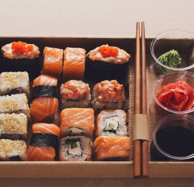 Set of sushi maki and rolls closeup in carton delivery box
