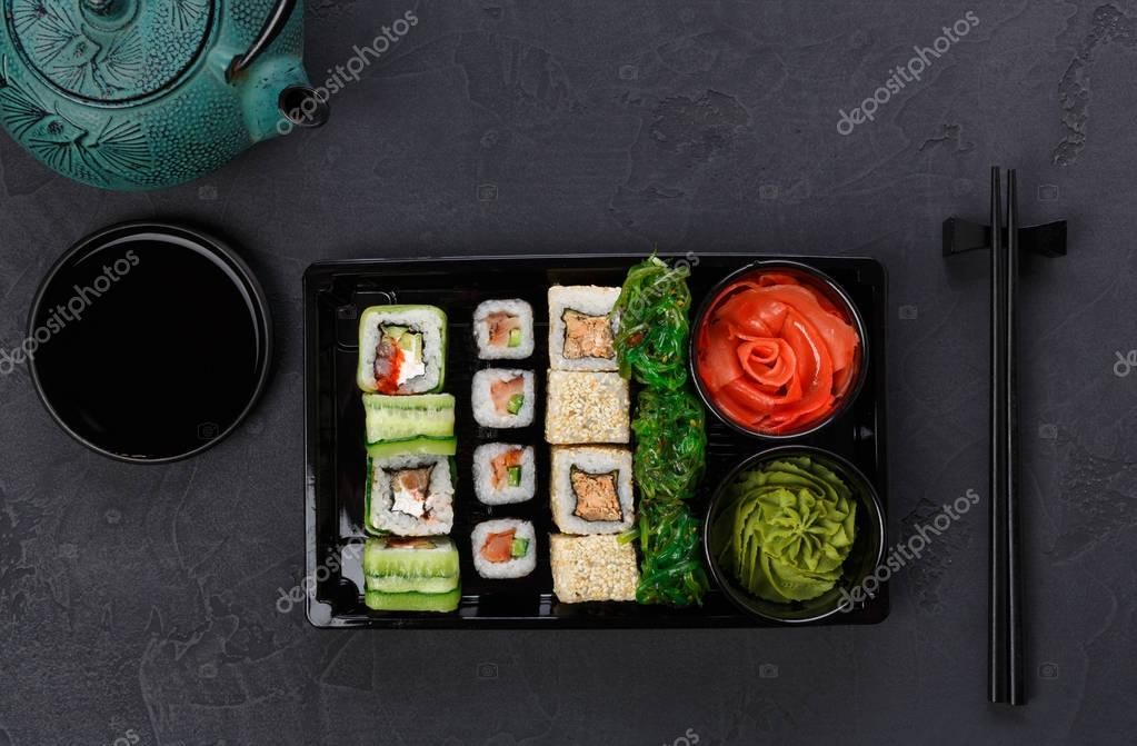 Set of sushi maki and rolls closeup in delivery box
