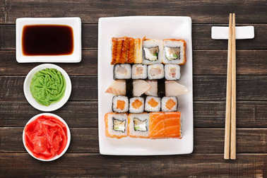 Set of sushi, maki and rolls on brown wooden background
