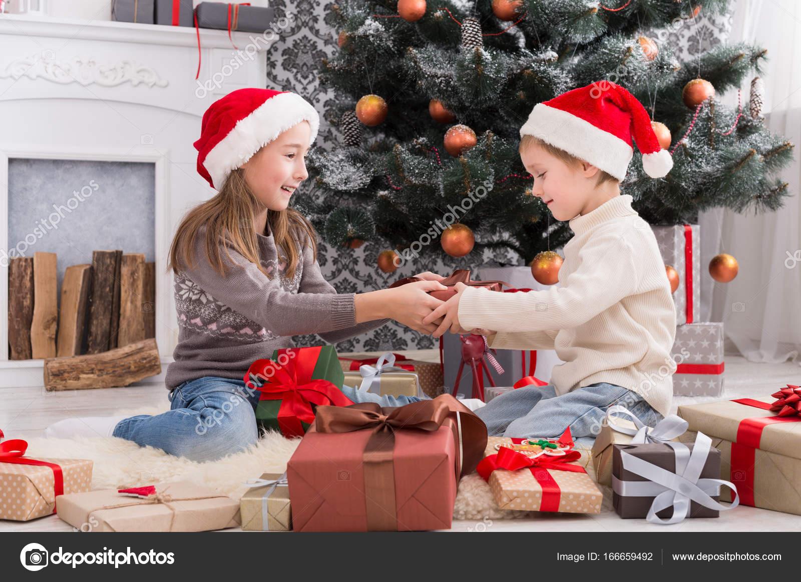 Gelukkige kinderen in santa hoeden uitpakken kerstcadeautjes