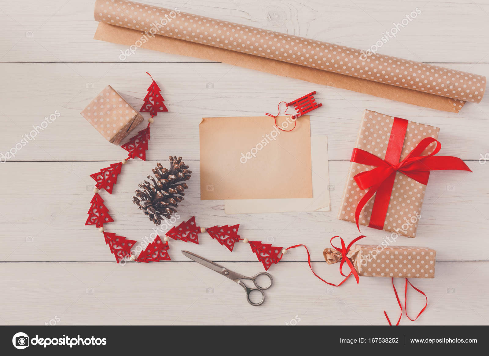 handmade tools for making christmas present box in craft paper with red ribbon top view of white wooden table with copy space on sheet of paper