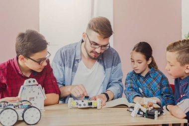 Stem education. Kids creating robots with teacher