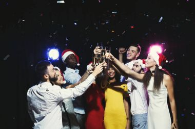 Group of young people celebrating new year with champagne at night club