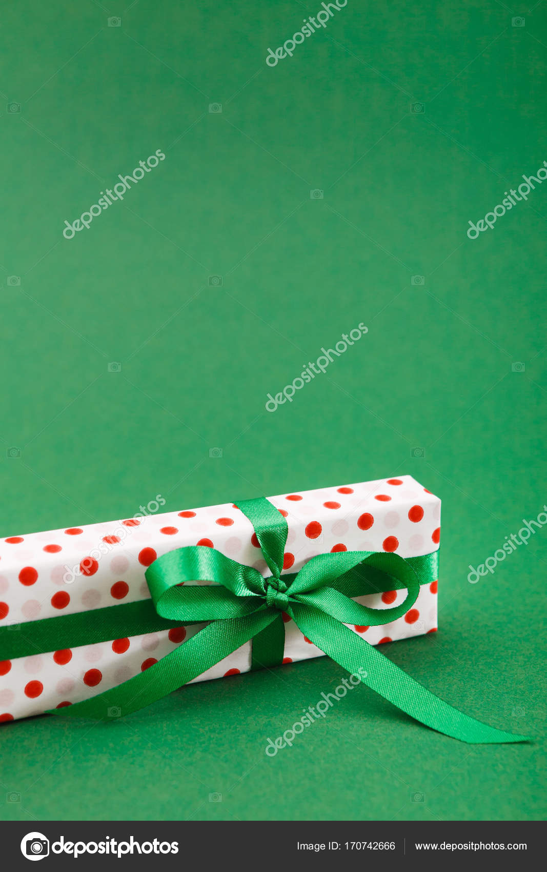 Handmade Christmas Gift Box In Dotted Paper With Green Ribbon On Background Copy Space Vertical Birthday Or Valentine Day Present