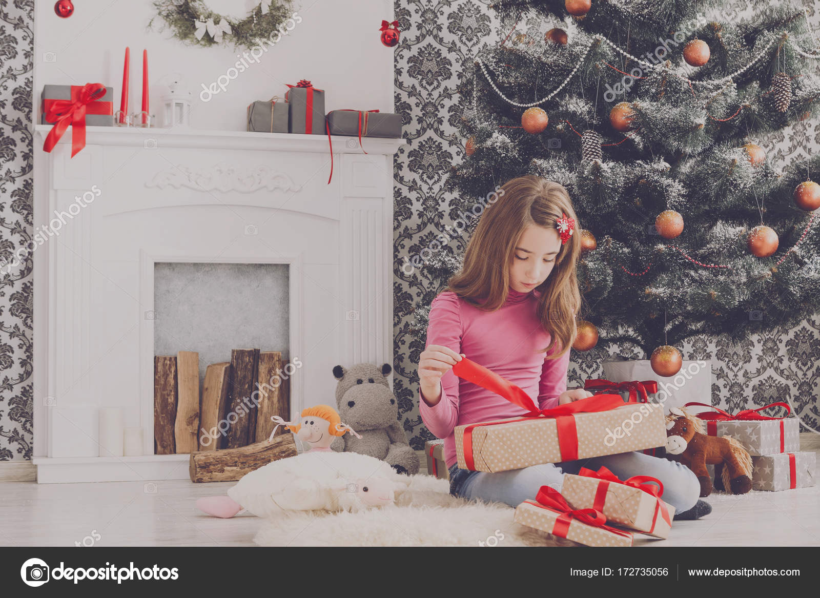 Schattig meisje uitpakken kerstcadeaus u stockfoto milkos