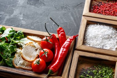 Cooking ingredients and herbs in wooden box on dark background