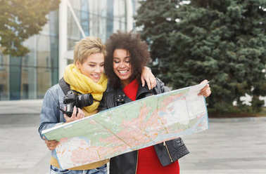 Two girl friends outdoors with paper city map