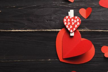 Valentine background with handmade paper hearts and spotted clothespin on black rustic wood. Happy lovers day card mockup, copy space stock vector