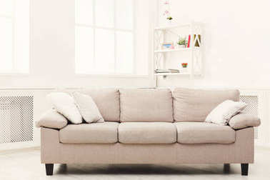 Beige couch with pillows in white modern interior, copy space on window background. Contemporary apartment design stock vector