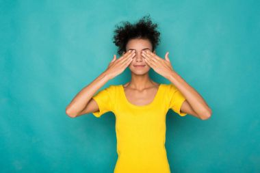 See no evil concept. Portrait of young african-american woman covering eyes with hands while standing against blue studio background. Confused girl close eyes with palms ignoring something stock vector
