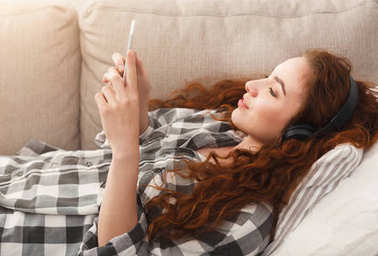 Young woman in headphones on beige couch