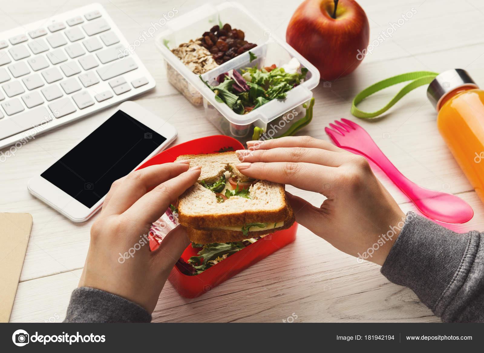 Pranzo Ufficio Vegano : Donna che mangia panino sano dalla scatola di pranzo al suo tavolo