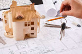 Architekt držení klíče na house modelu v úřadu