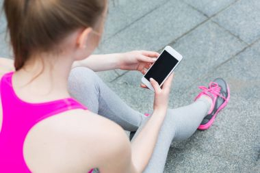 Sporty woman holding smartphone with copy space