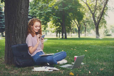 Young redhead woman in earphones chatting on mobile sitting under a tree