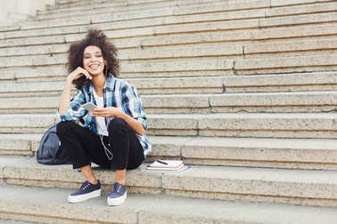 Young girl listening to music on university stairs