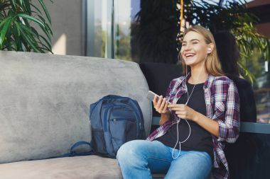 Young girl listening to music sitting in cafe