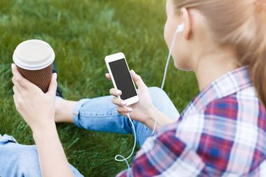 Young woman listening to music on grass outdoors