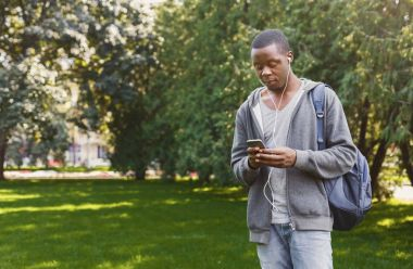 African-american student listening to music in park outdoors
