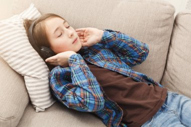 Girl listening music in headphones on couch