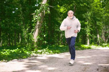 Elderly man running in green forest, copy space