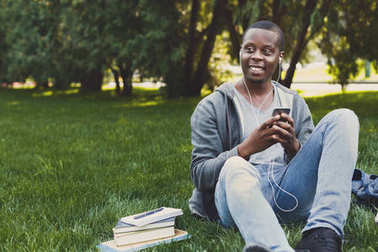 Smiling african-american student listening to music in park outdoors