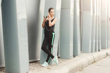 Cheerful sporty woman having rest after workout