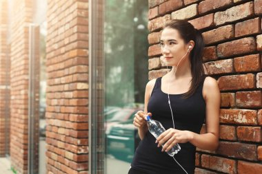 Woman runner is having break, drinking water
