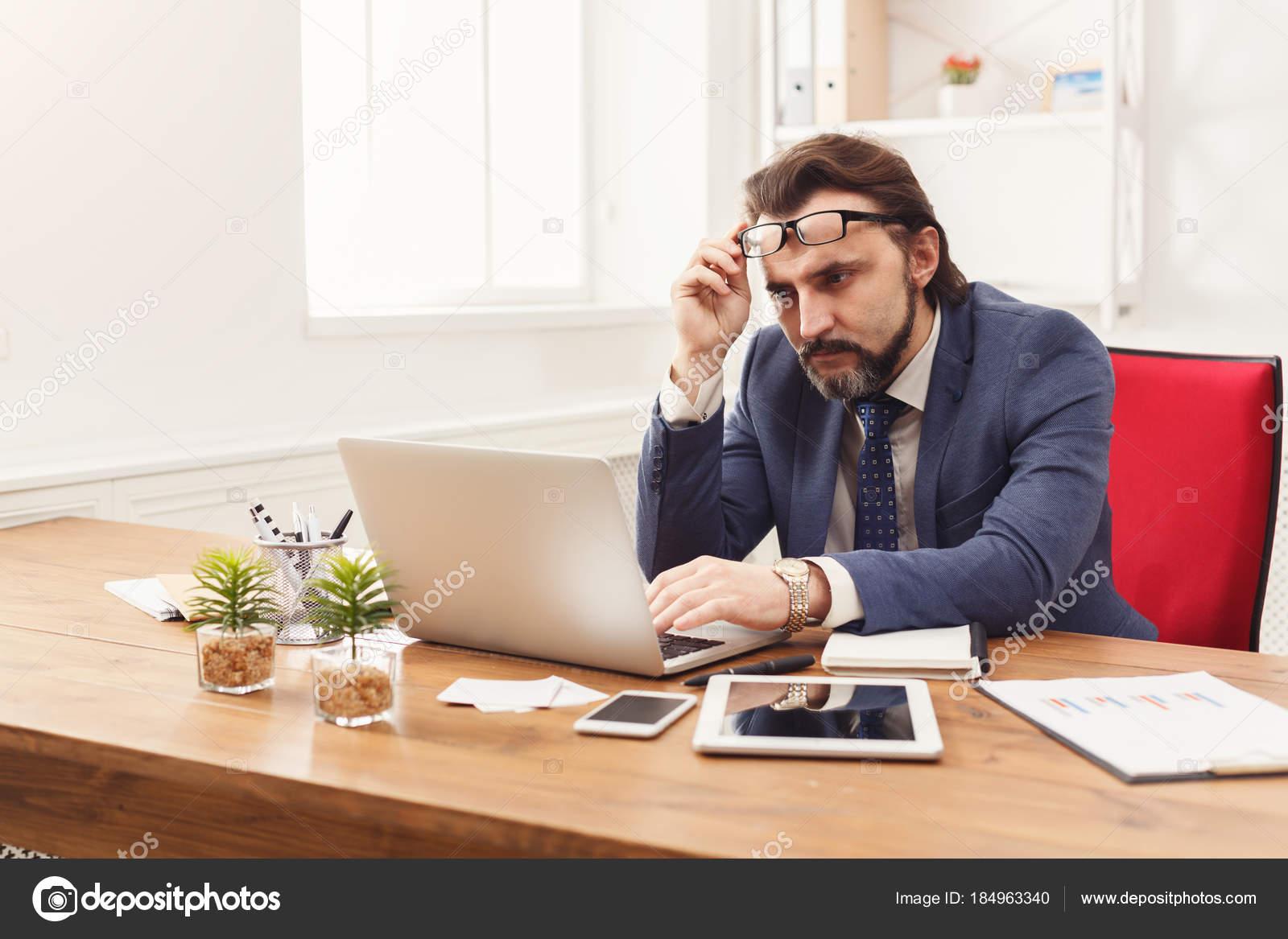 d1e137a3167d9 Concentrado hombre de negocios trabajando en ordenador portátil en interior  de oficina blanco. Considerado empleado en el trabajo con la computadora