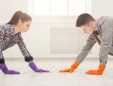 Young couple washing floor together