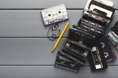Vintage cassettes and pencil to rewind tape on gray wooden background