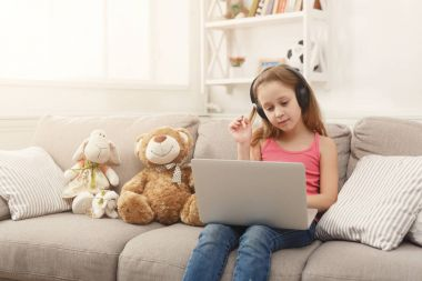 Cute little girl doing homework on laptop, sitting on couch in headphones