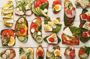 Variety of healthy vegetarian sandwiches on white wood, top view