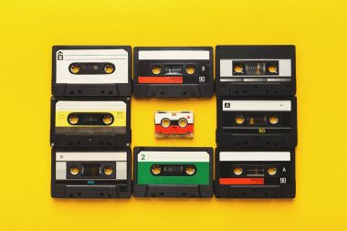 Big retro cassettes framing a small one on yellow background, top view, copy space
