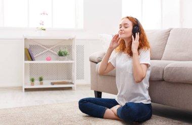 Young woman enjoying her favorite song in earphones