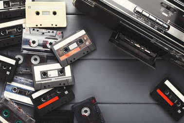 Heap of vintage audio cassettes and tape recorder at gray background