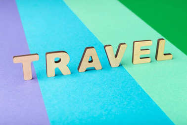 Word travel spelled with wooden letters on colorful background. Journey, vacation and holiday concept, copy space stock vector