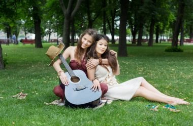 Two happy boho chic stylish girlfriends picnic in park