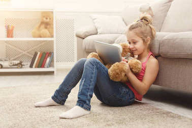 Little girl with tablet and teddy bear at home