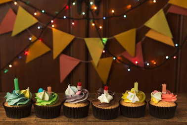 Chocolate cupcakes with candles against festive background