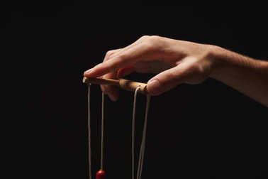 Manipulators hand with marionette string isolated on black