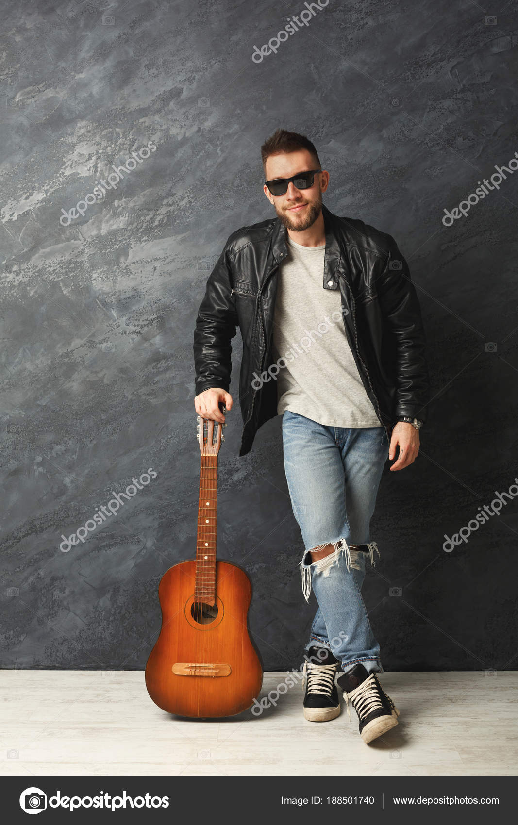 Handsome smiling man with guitar posing in studio — Stock