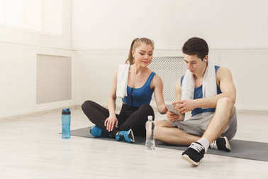 Fit couple with smartphone listening to music