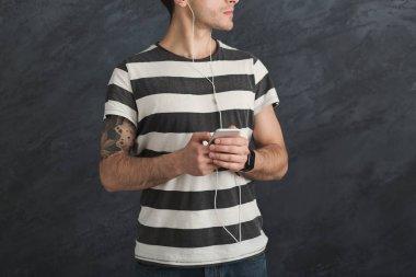 Man listen to music in earphones, studio shot