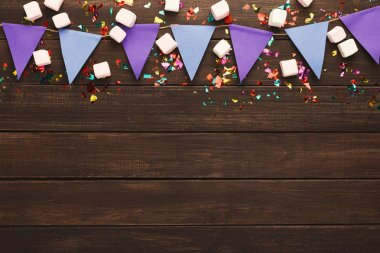 Border of violet paper flags garland, marshmallows and confetti on rustic wood. Birthday party decoration background, top view, copy space. Mockup for greeting card stock vector