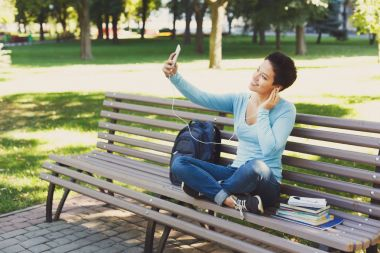 Shorthaired woman making selfie outdoors