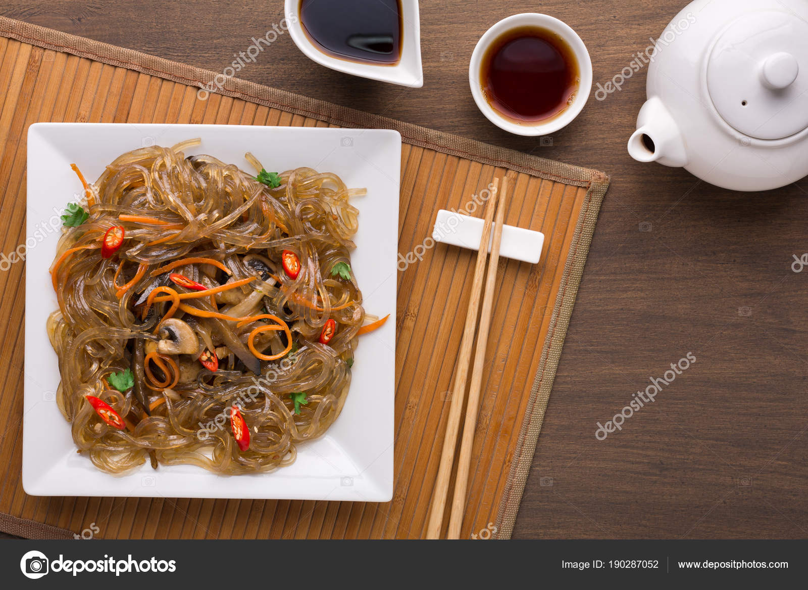 Asian restaurant menu mockup. Glass noodles with meat and vegetables on square platter served with soy sauce teapot and chopsticks on bamboo napkin on ... & Funchoza salad on square plate on wooden table u2014 Stock Photo ...